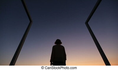 Silhouette of young woman raising up hands to the sky on the twilight. Modern high-tech bridge on background