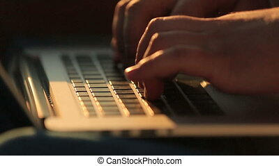 Close up of man hands typing on a laptop keyboard on sunset background
