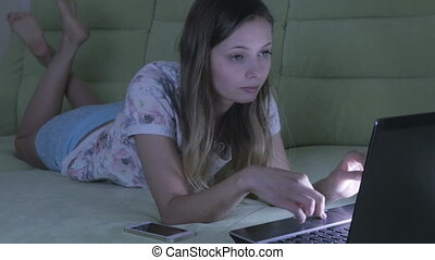 Beautiful girl lying on couch working at his laptop. She...