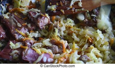 Cooking vegetables in a pan cabbage with meat.