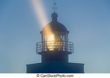 Lighthouse tower in the night with strong light beam