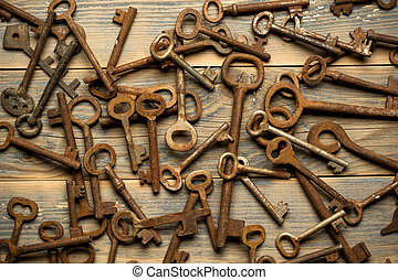 Many old keys on a well used wooden desk - Many old keys on...