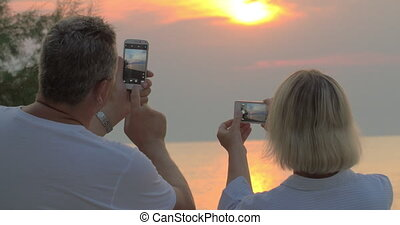 People Shooting Sea Sunset at Smartphones - Man and woman...