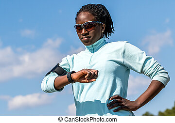 African teen sports woman reviewing results on smart watch.