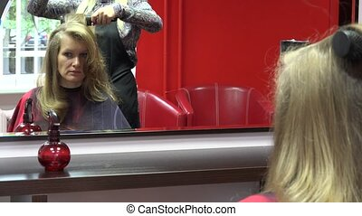 Hair dresser make hairstyle for blonde customer with comb...