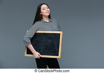 Happy woman holding blank black board over gray background