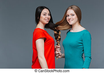 Two happy young women made one brair with their hair -...