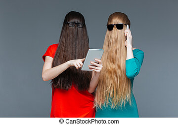 Two women with covered faces using tablet and cell phone