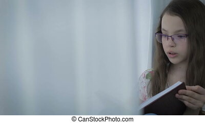 Beautiful little girl in glasses diligently does his...