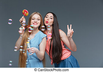 Two happy playful young women with colorful lollipop blowing...