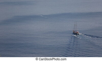 Sailing towards the red cliffs of the Santorini island with...