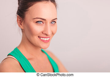 side of a smiling woman's face looking away from the camera...