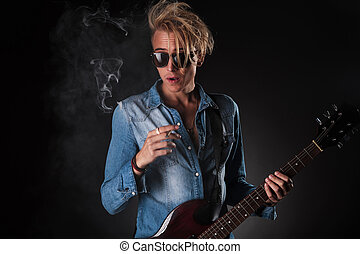amazed young guitarist smoking cigarette in studio while...