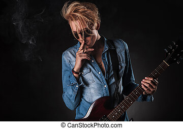 awesome young guitarist smoking and playing electric guitar...
