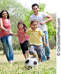 Happy family run to the soccer ball in the park, outdoor