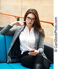 Confident business woman with phone in office