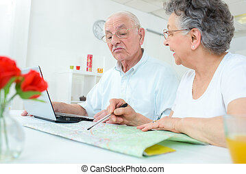 Elderly couple studying a map and using a notebook