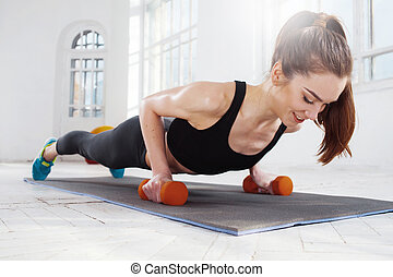 Beautiful slim brunette doing some push ups a the gym -...