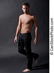 Fashion male model with black jean over black background