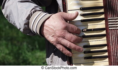 Old man plays on old accordion - Old man playing on worn old...