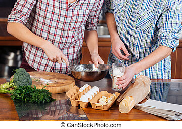 Hands of couple beating eggs and cooking together on kitchen...