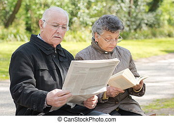 elderly couple reading in the park