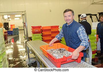 Man holding crate of fish