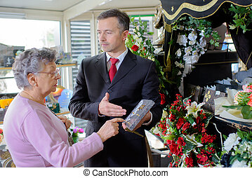 Funeral director showing woman a memorial plaque