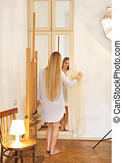 Blond bride looks in the mirror. Bridal morning