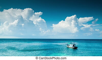 Lonely boat at blue sea under clouds