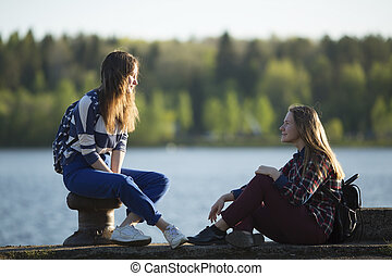 Two friends teen girls spend time together at the pier of...
