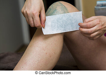 Amateur woman getting legs waxed for hair removal in home