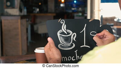 Man writing coffee price on chalk board - Man setting one...