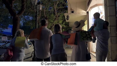 Big family walking in night street after shopping