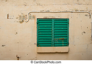 Wall with a window covered with green shutter