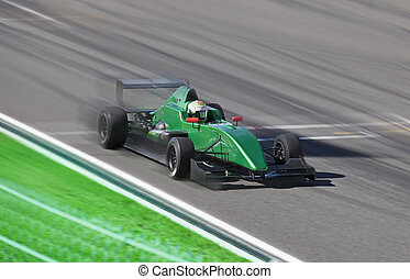 Formula 2 race car racing on a track with motion blur