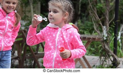 Girl blowing bubbles, suddenly her arms around the other...
