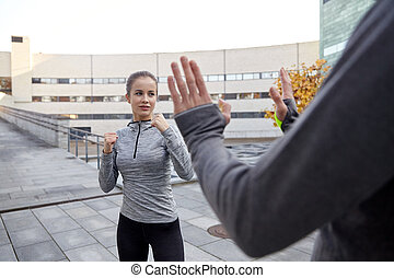 woman with trainer working out self defense strike -...