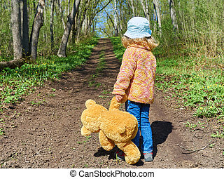child is walking down path with Teddy Bear - Little child is...