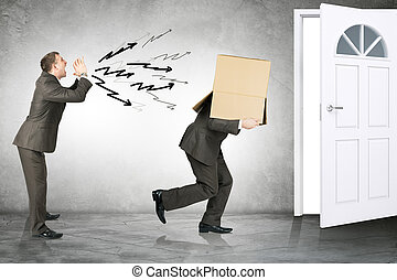 Business boss shouting to employee with box on his head and...