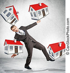Businessman holding little houses on grey background