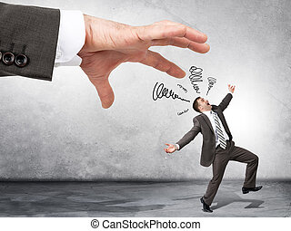 Business boss hand catching scared employee on grey wall...