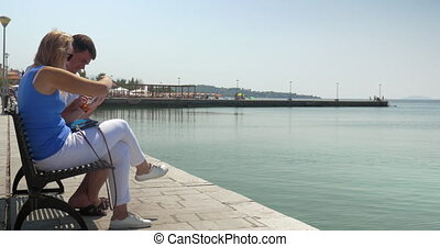 Man and woman using pad sitting on waterfront bench - Young...