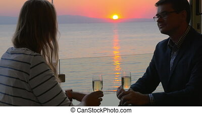 Couple on romantic date at seaside cafe - Young man and...