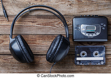 Headphones, player and retro compact cassette over wooden...