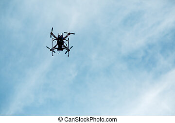 flying drone with camera on the sky. Silhouette of copter in...