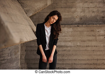 Young brunet woman standing outside in black jacket, jeans horizontal
