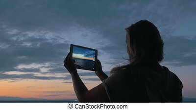 Woman with pad making photos of sea and sky in the dusk