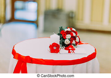 Wedding bouquet of white and red roses laying on a table with ribbon. Close-up view