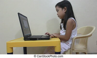 A child reading playing on a laptop - A long-haired child...